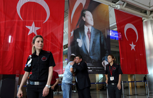 Men greet each other in front of Turkish flag and picture of modern Turkey's founder Mustafa Kemal Ataturk at Istanbul Ataturk airport, Turkey, following yesterday's blast June 29, 2016. (Photo by Goran Tomasevic/Reuters)