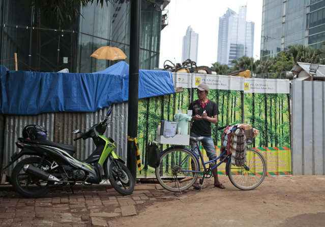 In this Friday, October 14, 2016 photo, a coffee vendor waits for customers near a patch of metal sheets adorned with stickers depicting a forest used to cover a construction site in Jakarta, Indonesia. The capital's fondness for fake greenery creates a n irony as the country is known for cutting down its precious tropical forests at a record rate. (Photo by Dita Alangkara/AP Photo)