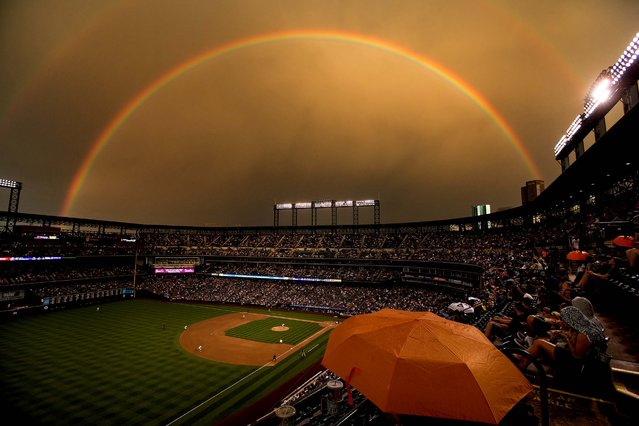 Fans sit under the cover of an umbrella as a rainbow illuminates Coors Field as the Colorado Rockies face the Pittsburgh Pirates in Denver, on Jule 25, 2014. (Photo by Justin Edmonds/Getty Images)