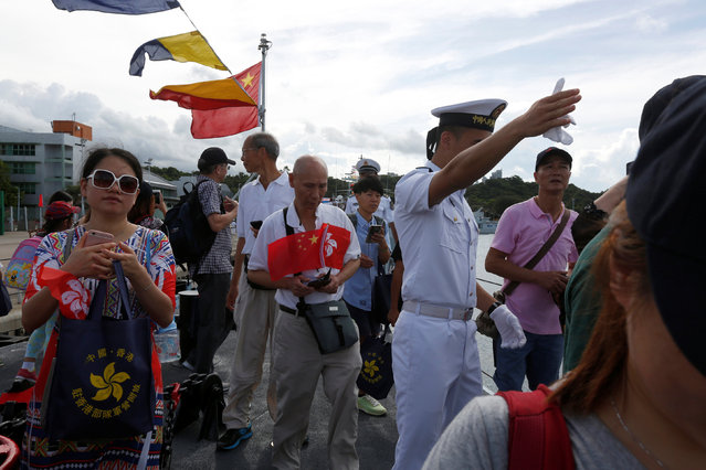 A People's Liberation Army naval soldier guides visitors on board a military vessel at a naval base during an open day celebrating the 19th anniversary of Hong Kong's handover to Chinese sovereignty from British rule, in Hong Kong July 1, 2016. (Photo by Bobby Yip/Reuters)