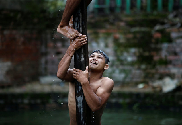 A devotee helps his friend to climb the wooden pole in between the pond while participating in the Deopokhari festival in Khokana, Nepal August 9, 2017. During the annual festival, a live goat is thrown into a pond and the team of devotees that retrieves the animal first wins. (Photo by Navesh Chitrakar/Reuters)