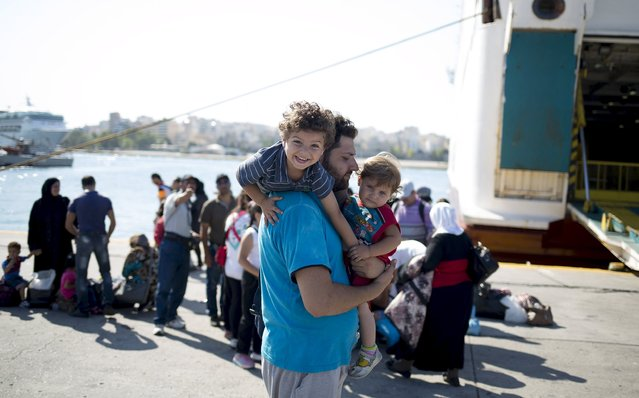 """A Syrian refugee man plays with children following their arrival onboard """"Eleftherios Venizelos"""" passenger ship at the port of Piraeus near Athens, Greece, August 20, 2015. (Photo by Stoyan Nenov/Reuters)"""