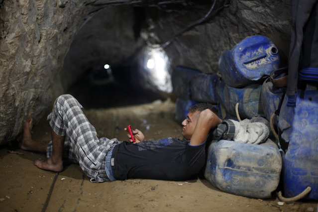 A Palestinian tunnel worker uses his mobile as he rests inside a smuggling tunnel beneath the Gaza-Egypt border in the southern Gaza Strip July 19, 2013. (Photo by Ibraheem Abu Mustafa/Reuters)