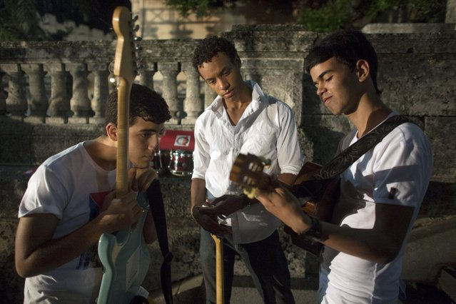 Students of the National School of Music, (R-L) Ernesto Robles, 18, Juan Carlos Poveda, and Antonio Gonzalez, 19, practice with their instruments before a performance during a public demonstration in support of Venezuela's government in Havana, March 15, 2015. (Photo by Alexandre Meneghini/Reuters)