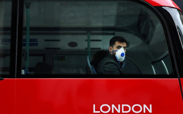A man wears a mask while sitting on a bus, as the number of coronavirus cases grow around the world, in central London, Britain on March 14, 2020. (Photo by Dylan Martinez/Reuters)
