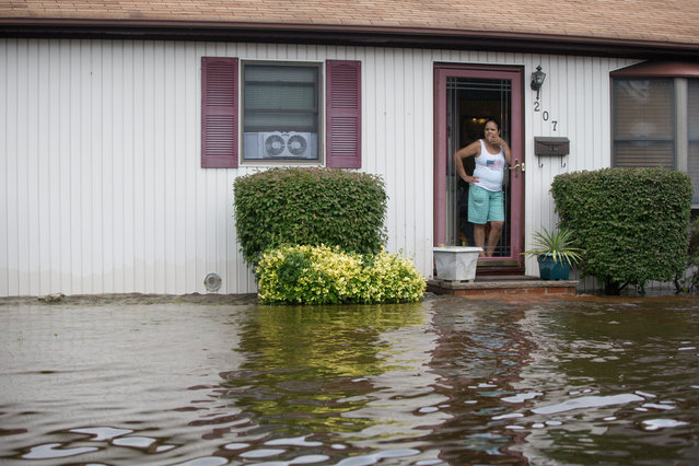 A woman stands at her doorway watching the water level rise on Moffit Blvd. following heavy rains and flash flooding August 13, 2014 in Islip, New York. The south shore of Long Island along with the tri-state region saw record setting rain that caused roads to flood entrapping some motorists. (Photo by Andrew Theodorakis/Getty Images)