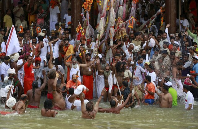 Sadhus or Hindu holy men take a dip in the Godavari river during the first Shahi Snan (grand bath) at Kumbh Mela, or Pitcher Festival in Nashik, India, August 29, 2015. (Photo by Danish Siddiqui/Reuters)