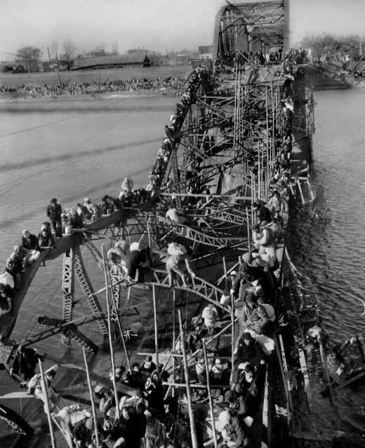 Residents from Pyongyang, North Korea, and refugees from other areas crawl perilously over shattered girders of the city's bridge on December 4, 1950, as they flee south across the Taedong River to escape the advance of Chinese Communist troops. The Chinese entered the Korean War as allies of North Korea.  (Photo by Max Desfor/AP Photo)