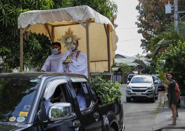 Residents wave plants as a Catholic priest holding a Monstrance with the Sacred Host rides a pick-up truck around villages during a new Palm Sunday ritual to help prevent the spread of the new coronavirus in Manila, Philippines on Sunday, April 5, 2020. Catholic devotees usually troop to churches on Palm Sunday to have their palm fronds blessed to commemorate the entry of Jesus Christ into Jerusalem. (Photo by Aaron Favila/AP Photo)