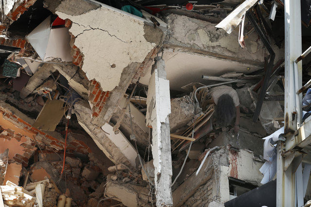 The body of woman hangs crushed by a collapsed building in the neighborhood of Roma Norte, in Mexico City, Tuesday, September 19, 2017. Throughout Mexico City, rescue workers and residents dug through the rubble of collapsed buildings seeking survivors following a 7.1 magnitude quake. (Photo by Marco Ugarte/AP Photo)