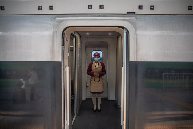 A train attendant wearing a protective face mask stands on a train to Wuhan, at the railway station in Beijing, China, 29 March 2020. Wuhan, the epicenter of the coronavirus outbreak, partly lifted the lockdown allowing people to enter the city after more than two months. Chinese authorities eased the quarantine measures as cases of Covid-19 across China have plummeted, according to Chinese government figures. (Photo by Roman Pilipey/EPA/EFE)