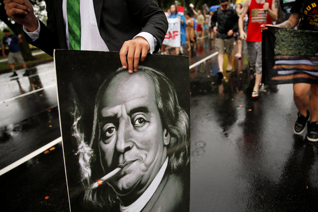 A poster depicting Benjamin Franklin smoking a joint is seen as a group of cannabis advocates smoke marijuana and march down Broad Street toward the Wells Fargo Center on the final day of the Democratic National Convention in Philadelphia, Pennsylvania, U.S., July 28, 2016. (Photo by Dominick Reuter/Reuters)