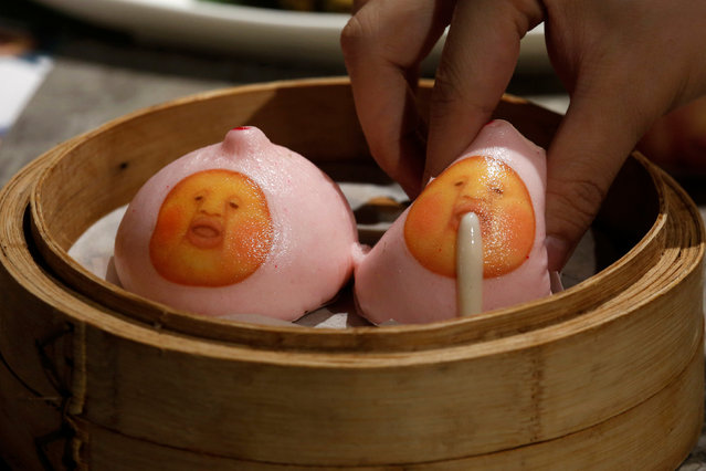 "A milk custard bun made to resemble one of the popular Japanese ""Kobitos"" characters is squeezed during a display for the photographer at Dim Sum Icon restaurant in Hong Kong, China July 25, 2016. A dim sum restaurant in Hong Kong encourages diners to play with their food, and the result will either disgust or delight you. At Dim Sum Icon customers can squeeze a strange creature to poo or vomit on their plate before eating it. Hungry punters poke a hole into the mouth – or the rear – of the dim sum with a chopstick, squeeze it and watch the brown or white cream ooze out. (Photo by Bobby Yip/Reuters)"