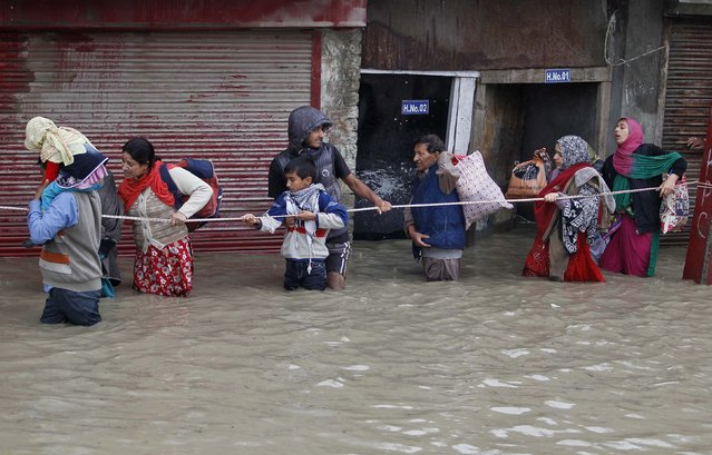 Kashmiri people walk with the help of a rope through a flooded street during rain in Srinagar September 6, 2014. (Photo by Danish Ismail/Reuters)