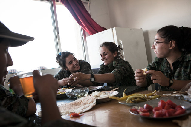 YPJ soldiers eat a breakfast of peppers, tomatoes, cheese, flatbread and tea at their post near the Syrian-Kurdistan border in Til Kocer, Syria on August 9, 2014. YPJ meals are often modest since most of their supplies, including food, are donated from local community members. (Photo by Erin Trieb/NBC News)