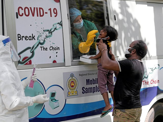 A girl reacts as health official uses a swab to collect a sample in a village during the curfew amid concerns about the spread of coronavirus disease (COVID-19), in Colombo, Sri Lanka, April 18, 2020. (Photo by Dinuka Liyanawatte/Reuters)