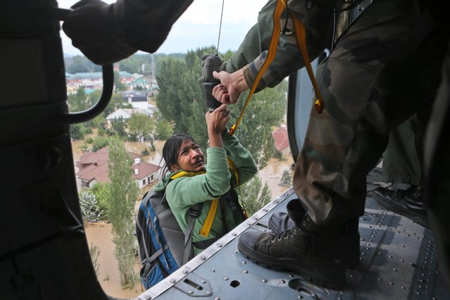 An Indian tourist cries as she is airlifted into a chopper in Srinagar, India, Tuesday, September 9, 2014. The death toll from floods in Pakistan and India reached 400 on Tuesday and have put more than half a million people in peril and rendered thousands homeless in the two neighboring states. The tourist was stranded on the terrace of a five-storey hotel in central Srinagar. (Photo by Dar Yasin/AP Photo)