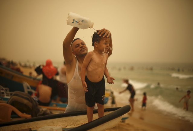 A Palestinian man washes his son on a beach along the Mediterranean Sea during a sandstorm in the northern Gaza Strip September 8, 2015. (Photo by Mohammed Salem/Reuters)