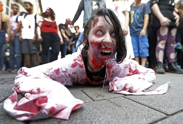 """A participant crawls on the ground during a """"Zombie Walk"""" in Strasbourg September 13, 2014. (Photo by Vincent Kessler/Reuters)"""