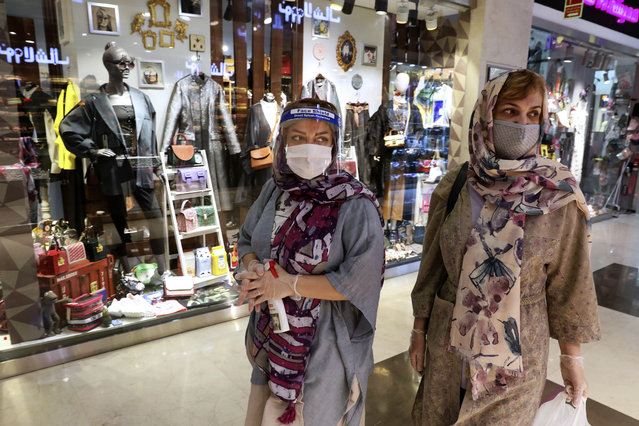 Women wearing protective face masks and gloves to help prevent the spread of the coronavirus shop at the Kourosh Shopping Center in Tehran, Iran, Monday, April 20, 2020. Iran on Monday began opening intercity highways and major shopping centers to stimulate its sanctions-choked economy, gambling that it has brought under control its coronavirus outbreak – one of the worst in the world – even as some fear it could lead to a second wave of infections. (Photo by Vahid Salemi/AP Photo)