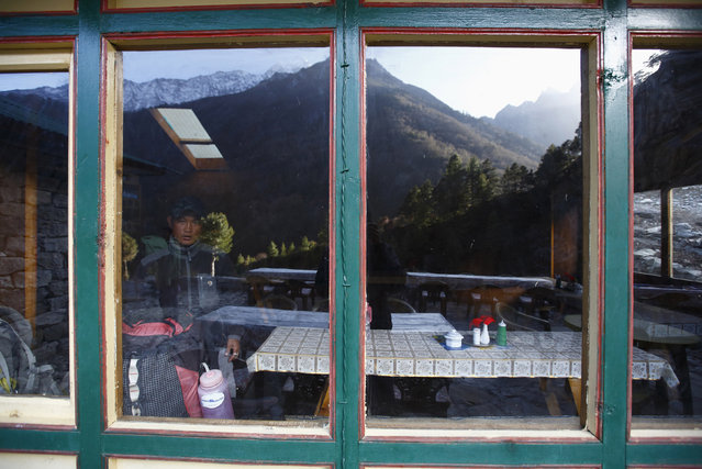 Porter and climber Tenzing Bhotay Sherpa, 31, looks through the window of a lodge after arriving from Everest base camp, in Phunki Tenga in Solukhumbu District April 30, 2014. (Photo by Navesh Chitrakar/Reuters)