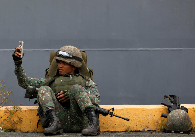 A Philippine marine soldier takes a selfie with his phone during their arrival from Marawi at port area in metro Manila, Philippines October 30, 2017. (Photo by Dondi Tawatao/Reuters)