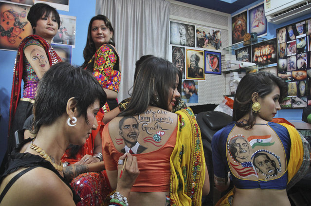 Indian women get their backs painted with portraits of U.S. President Barack Obama and Indian Prime Minister Narendra Modi in Ahmadabad, India, Friday, September 26, 2014. Modi left for his five-day visit to the United States, starting Friday during which he will address the U.N. General Assembly, hold talks with Obama and a slew of top American officials, interact with the heads of major U.S. companies and influential Indian-Americans. (Photo by Ajit Solanki/AP Photo)