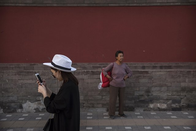 A Chinese woman uses her smartphone as she walks near the Drum Tower on September 18, 2014 in central Beijing, China. (Photo by Kevin Frayer/Getty Images)