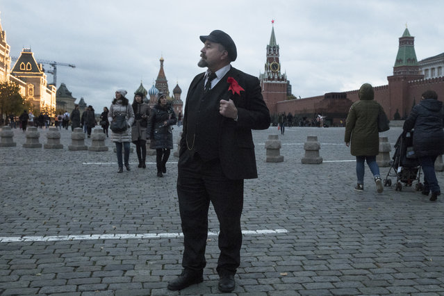 In this photo taken on Wednesday, October 11, 2017, Sergei Soloviev, who impersonates Soviet founder Vladimir Lenin, stands in Red Square, with St. Basil's Cathedral, center, Spasskaya (Saviour) Tower, and the Lenin's Mausoleum in the background, in Moscow, Russia. Visitors are forbidden to photograph Vladimir Lenin's mummified body in the mausoleum on Red Square – but nearby, Sergei Soloviev is happy to offer an alternative. (Photo by Pavel Golovkin/AP Photo)