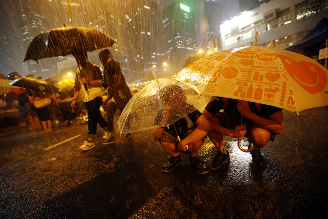 Protesters take shelter from the rain under umbrellas as they block the main street to the financial Central district outside of the government headquarters in Hong Kong, September 30, 2014. (Photo by Carlos Barria/Reuters)