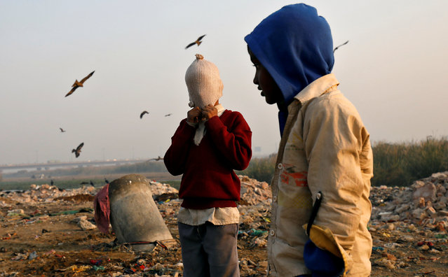 A boy covers his face with a woollen hat on the banks of the Yamuna river in Delhi, India, November 24, 2017. (Photo by Saumya Khandelwal/Reuters)