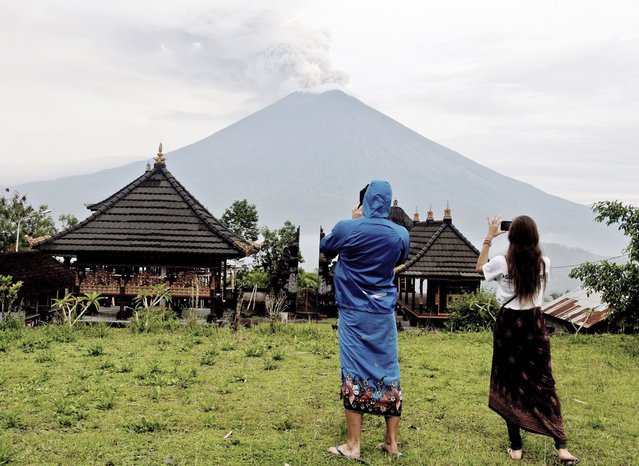 Foreign tourists take pictures of Mount Agung as it erupts in Karangasem, Bali, Indonesia, Wednesday, November 29, 2017. Authorities have told tens of thousands of people to leave an area extending 10 kilometers (6 miles) from the volcano as it belches volcanic materials into the air. Mount Agung's last major eruption in 1963 killed about 1,100 people. (Photo by Lukman S. Bintoro/AP Photo)