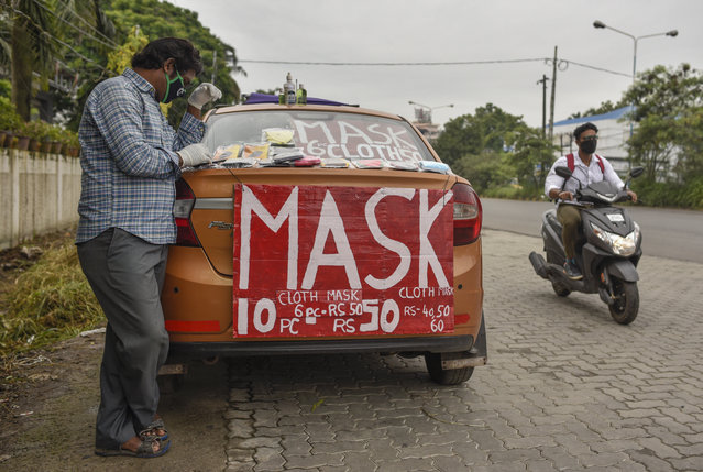 An Indian cab driver who has been out of work due to the COVID-19 pandemic, sells face masks from his car by a roadside in Kochi, Kerala state, India, Thursday, July 2, 2020. (Photo by R.S. Iyer/AP Photo)