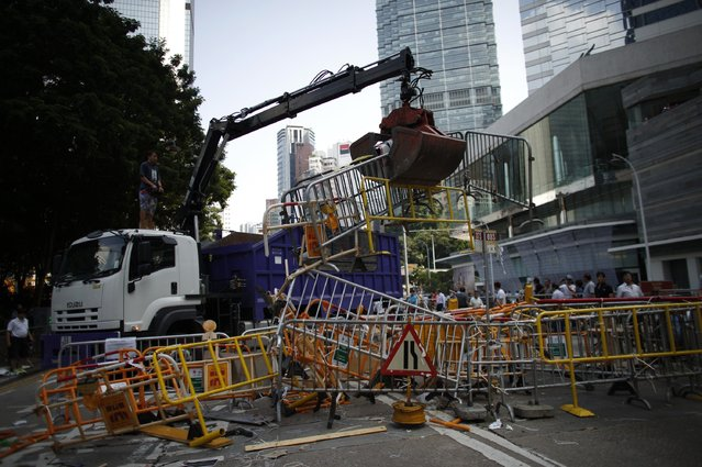 A crane removes barricades from the main protest site in Admiralty in Hong Kong October 13, 2014. (Photo by Carlos Barria/Reuters)