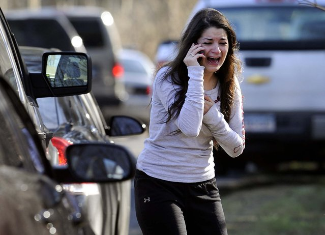 A woman waits to hear about her sister, a teacher, following a shooting at the Sandy Hook Elementary School in Newtown, Connecticut. A man killed his mother at their home and then opened fire inside the elementary school where she taught, massacring 26 people, including 20 children, as youngsters cowered in fear to the sound of gunshots reverberating through the building and screams echoing over the intercom. (Photo by Jessica Hill/Associated Press)