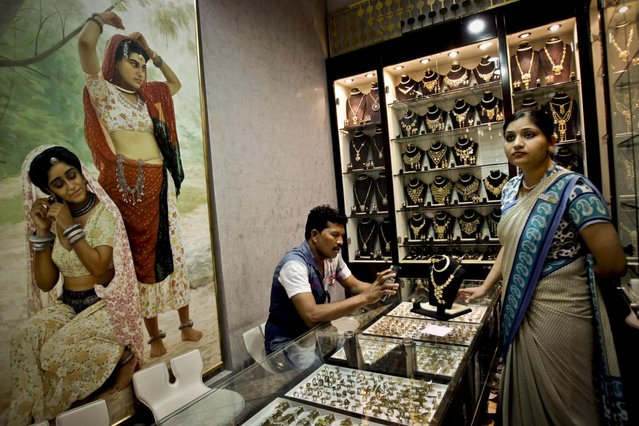 A customer uses his calculator to convert  a jewelry price at a jewelry shop in the gold suq in Dubai, United Arab Emirates. (Photo by Kamran Jebreili/AP Photo)