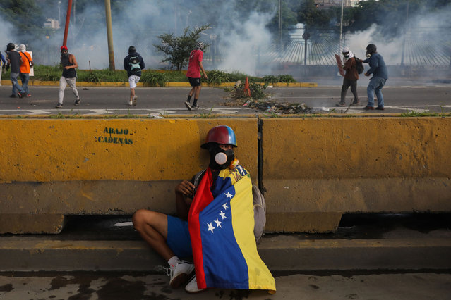 A protester hides behind a wall during protests in Caracas, Venezuela, 22 June 2017. Venezuela has seen waves of protests for and against the government, some of which have turned violent leaving at least dozens of deaths and hundreds wounded, according to the to the Attorney's Office. (Photo by Miguel Gutierrez/EPA/EFE)