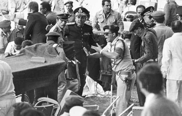 An Egyptian security guard screams at people as medics bring in a stretcher to carry the wounded after the attack which killed President Anwar Sadat, October 6, 1981, as he watched a military parade. (Photo by AP Photo)