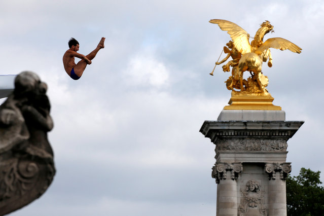 A participant dives from the Pont Alexandre III bridge into the River Seine in Paris, France, June 23, 2017. Paris transformed into a giant Olympic park to celebrate International Olympic Day with a variety of sporting events for the public, as the city bids to host the 2024 Olympic and Paralympic Games. (Photo by Jean-Paul Pelissier/Reuters)