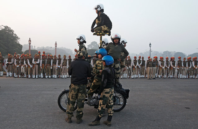 """Border Security Force (BSF) """"Daredevils"""" women motorcycle riders perform as others watch during a rehearsal for the Republic Day parade on a winter morning in New Delhi, January 11, 2018. (Photo by Adnan Abidi/Reuters)"""