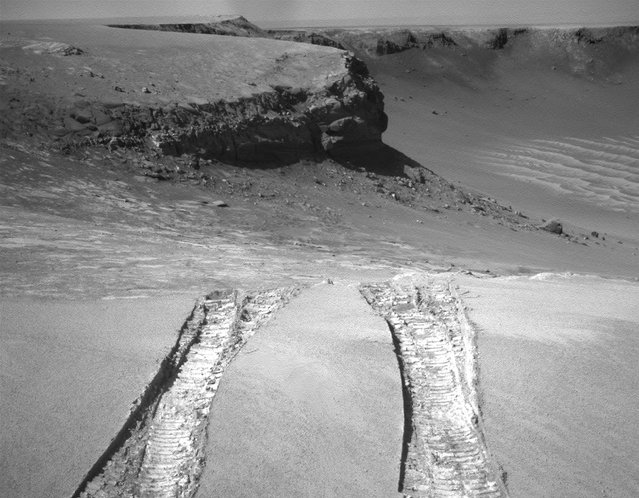 Opportunity climbs out of Victoria Crater on August 28, 2008, following the tracks it had made when it descended into the 800-meter-diameter (half-mile-diameter) bowl nearly a year earlier. The rover's navigation camera captured this view back into the crater just after finishing a 6.8-meter (22-foot) drive that brought Opportunity out onto level ground during the mission's 1,634th Martian day, or sol. (Photo by AP Photo/NASA/The Atlantic)