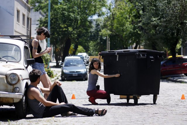 """Rocio Mendez Brisighelli (C) operates a pinhole camera made out of a street's dumpster before taking a self-portrait along with fellow members of the visual arts group """"Bazofia"""", Rodrigo Aguero (bottom L) and Natacha Ebers, in Buenos Aires November 8, 2014. (Photo by Marcos Brindicci/Reuters)"""