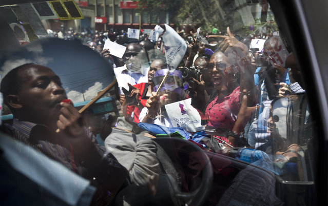 Kenyan women protest for the right to wear whichever clothes they want, accompanied by a male supporter, left, seen reflected and through the windows of a minibus, at a demonstration in downtown Nairobi, Kenya Monday, November 17, 2014. (Photo by Ben Curtis/AP Photo)