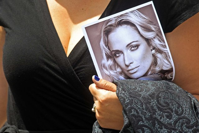 A woman holds a photo of Reeva Steenkamp, as she leaves her funeral,  in Port Elizabeth, South Africa, February 19, 2013. Olympic athlete Oscar Pistorius is charged with Steenkamp's murder on Valentine's Day. The defense lawyer says it was an accidental shooting. (Photo by Schalk van Zuydam/Associated Press)
