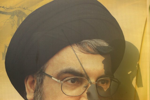 A Muslim Shi'ite boy is seen through a picture of Lebanon's Hezbollah leader Sayyed Hassan Nasrallah as he takes part in a march organised by Hezbollah during a re-enactment of the battle of Kerbala during a mourning process, ahead of the day of Ashoura, in Saksakieh village, southern Lebanon, October 18, 2015. (Photo by Ali Hashisho/Reuters)