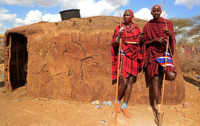 Maasai men of Matapato clan stand outside a manyatta house after attending the Olng'esherr (meat-eating) passage ceremony to unite two age-sets; the older Ilpaamu and the younger Ilaitete into senior elder-hood as the final rite of passage, after the event was initially postponed due to the coronavirus disease (COVID-19) outbreak in Maparasha hills of Kajiado, Kenya on September 23, 2020. (Photo by Thomas Mukoya/Reuters)