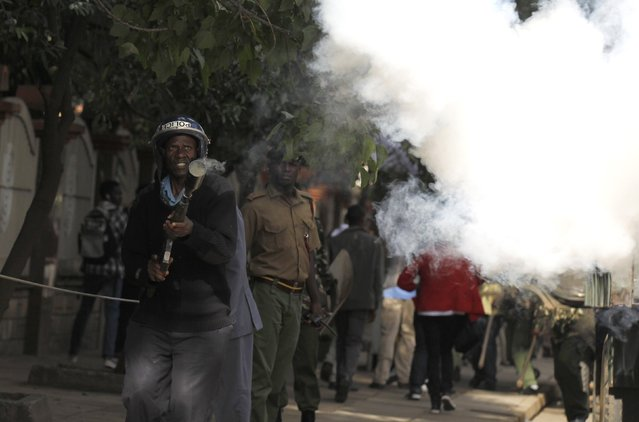 A riot police officer fires a teargas canister to disperse the #OccupyHarambeeAve demonstration in Kenya's capital Nairobi November 25, 2014. (Photo by Thomas Mukoya/Reuters)