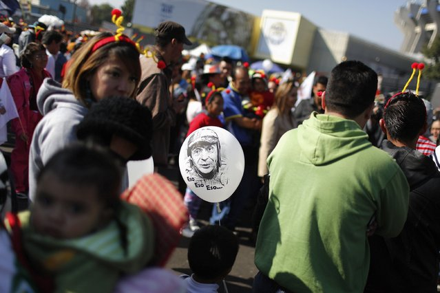 "A balloon with the face of  ""El Chavo del Ocho"", a character created by screenwriter Roberto Gomez Bolanos, is seen as people wait to enter the Azteca stadium for the mass in memory of Bolanos in Mexico City November 30, 2014. (Photo by Tomas Bravo/Reuters)"
