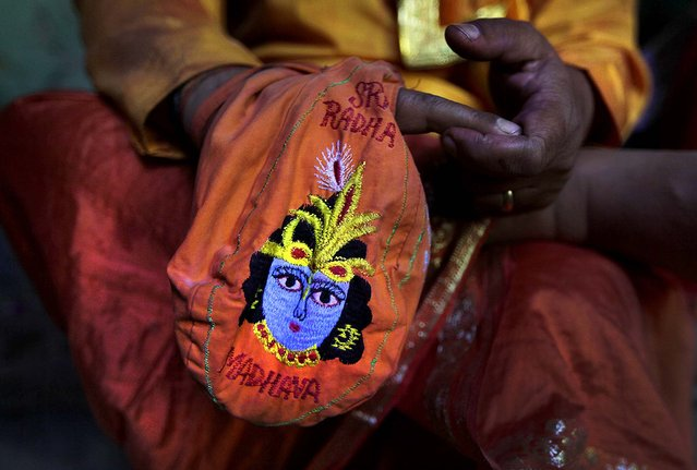 A priest prays holding a bag with an image of the Hindu God Krishna at the Ladali  in Barsana. (Photo by Manish Swarup/Associated Press)