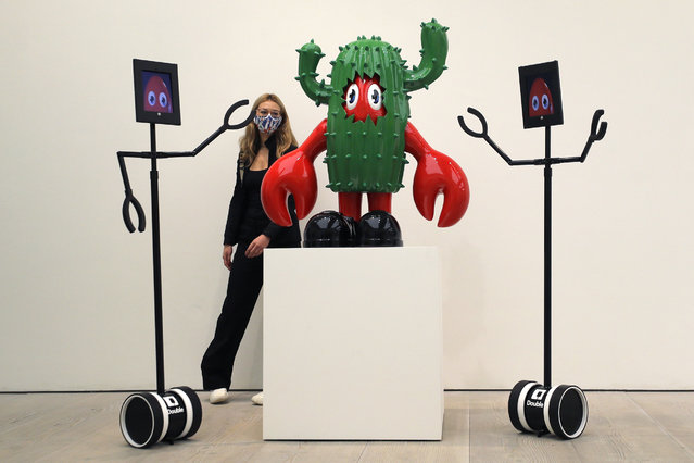A woman and remote controlled robots view a piece of artwork by artist Philip Colbert in the Lobsteropolis exhibition at the Saatchi Gallery in London, Thursday, October 29, 2020. Lobsteropolis offers audiences the chance to view artworks in situ, or digitally via robots from the comfort of their own home. (Photo by Kirsty Wigglesworth/AP Photo)